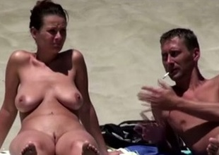 Comely brunette pet on the nudist beach sunbathing