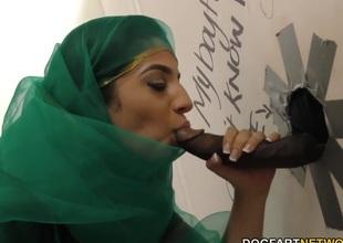 Nadia Ali having fun with coloured cock in a gloryhole