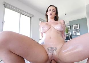 A brunette with a tattoo over her pussy is fucking on the bed